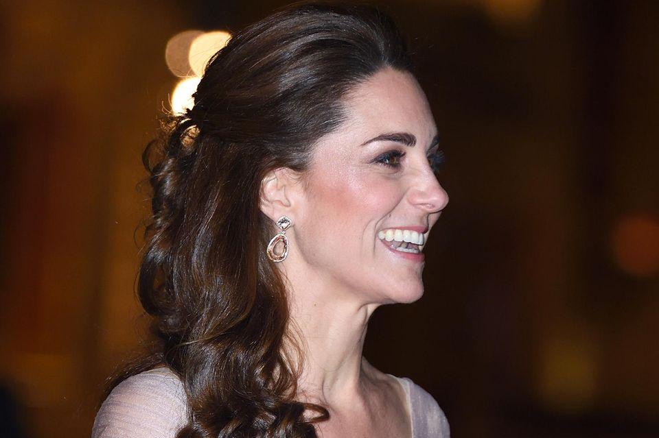 Herzogin Catherine wählt eine Hochsteckfrisur am Hinterkopf und trägt in den Längen leichte Wellen.
