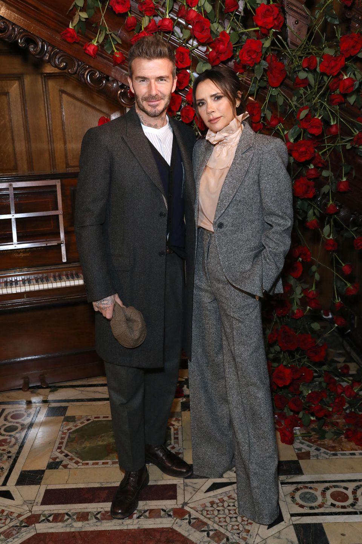 Januar 2019  Im eleganten Anzug-Lookbesuchen David und Victoria Beckham die Fashion Week in London. Um das knabenhafte Outfit aufzulockern, kombiniert die Modedesignerin eine Rüschenbluse in zartem Rosa zu ihrem Zweiteiler.