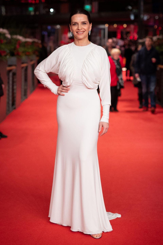 Juliette Binoche setzt auf eine weiße bodenlange Robe. Ihr dunkles Haar trägt sie hochgesteckt, dazu kombiniert sie glitzernde Ohrringe.