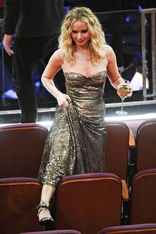 2018:  Die wohl spektakulärste Showeinlage der Veranstaltung liefert Jennifer Lawrence ab. Die Schauspielerin scheint keine große Lust auf Umwege durch die langen Stuhlreihen zu haben und klettert einfach über die Theatersitze. Dabei muss sie nicht nur ihr langes Abendkleid, sondern auch ihr gut gefülltes Weinglas händeln. Mit Erfolg: Sowohl Jennifer als auch das Glas kommen wohlbehalten am Ziel an.