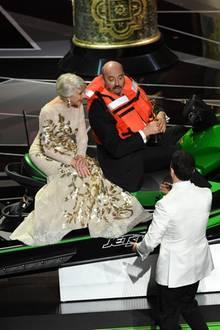 """2018:  Das wohl ungewöhnlichste Bühnenbild geben Helen Mirren und Mark Bridges ab. Der Kostümdesigner gewinnt an diesem Abend nicht nur einen Oscar für die Kostüme in """"Phantom Thread"""", sondern auch den unkonventionellsten Preis für die kürzeste Dankesrede des Abends: einen Jetski. Präsentiert wird die """"Trophäe"""" vonModerator Jimmy Kimmel undSchauspielerin Helen Mirren, die auch als Bridges erste Mitfahrerin fungiert."""