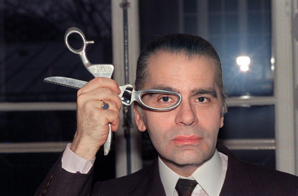 1987 posiert Karl Lagerfeld mit einer Schere in seinem Atelier.