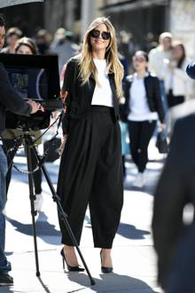 """Schwanger oder nicht? Model Heidi Klum zeigt sich am Set von """"Germany's next Topmodel"""" in einer weiten, schwarzen Hose, einem weißen T-Shirt und Lederjacke. Dazu kombiniert sie schwarze, schlichte Pumps. Ihr Outfit verrät nicht viel, ein Babybauch ist nicht eindeutig erkennbar - doch dann folgt eine Geste, die mehr als eindeutig ist!"""