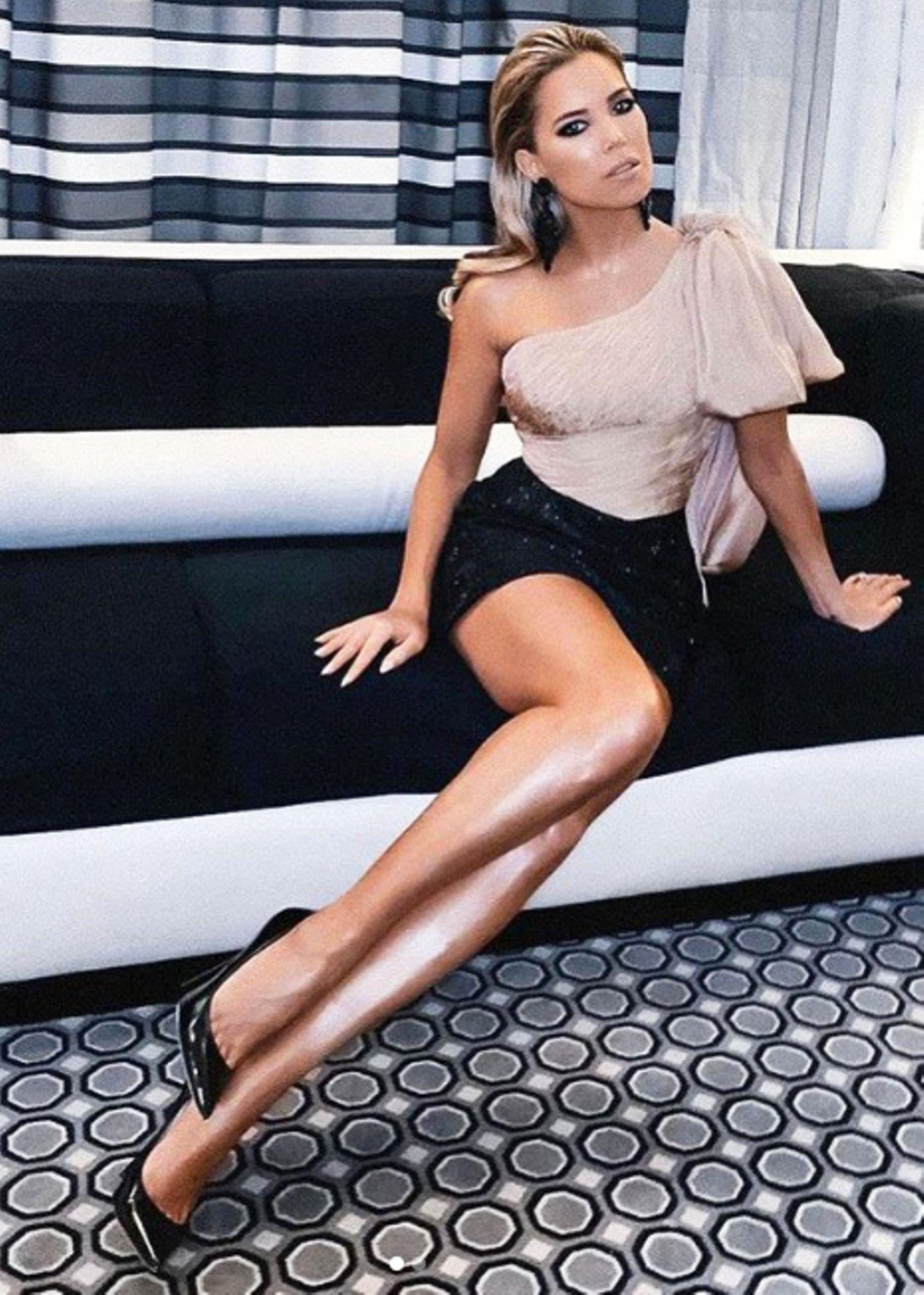 Sylvies Couture-Kleid ist eine Kreation bestehend aus einem schwarzen, glitzernden Mini-Rock und einem glamourösen One-Shoulder-Oberteil. Ihre trainierten, langen Beine funkeln mit ihrem Rock und ihrem Make-up-Glow um die Wette.