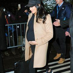 """So hüllt die Bald-Mama ihren schwangeren Bauch in eine Zip-Jackeaus der Umstandsmoden-Kollektion des Labels """"Ingrid & Isabel"""" für rund 80 Euro. Dazu trägt sie eine bequeme schwarze Leggings und schwarze """"UltraBoost""""-Sneaker von Adidas für etwa 150 Euro. Ihr Hab und Gut für die Reise packt Herzogin Meghan in einen schwarzen """"Le Sud""""Leder-Weekender von Cuyana für rund 350 Euro."""