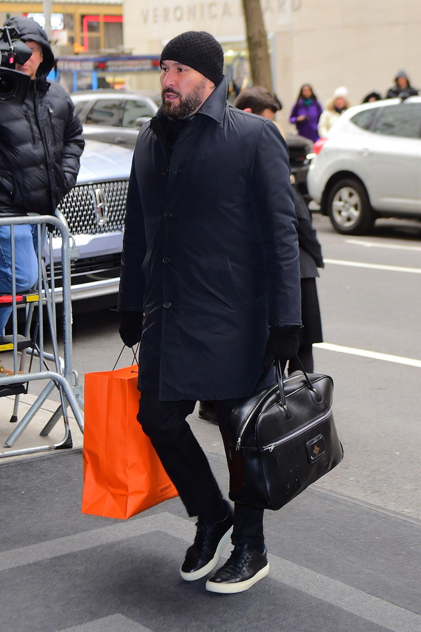 Hair Stylist Serge Normant folgt Daniel Martin auf dem Fuße. Für die anstehende Party hält er eine große Geschenktüte in leuchtendem Orange in der Hand.