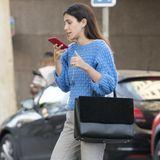 Alessandra de Osma zeigt sich privat sportlich und doch schick: Zu einem hellblauen Strickpullover und grauer Zigarettenhose kombiniert sie weiße Sneaker und eine schwarze, große Handtasche.