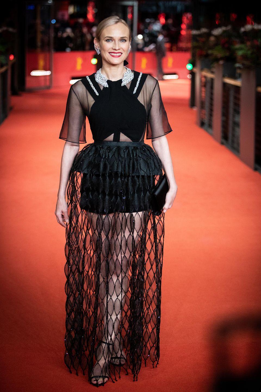 In einer spektakulären Robe von Givenchy Haute Couture hat Diane Kruger einen glänzenden Auftritt auf dem Red Carpet der Berlinale 2019. Das Kleid aus schwarzem Samt und Tüll wird dankdesglitzernden Kragens zu einem besonderen Hingucker.