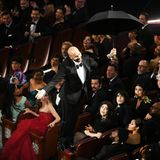 """Comedian Keegan-Michael Peele kündigt Bette Midler an, die ein Lied aus dem neuen """"Mary Poppins""""-Film singt. Dazu fliegt er an einem Regenschirm (und Drahtseilen) in das Dolby Theatre ein."""