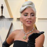 """Lady Gaga verteilt Küsschen auf dem roten Teppich. Um den Hals trägt sie den berühmten Tiffany Diamanten, der über 128 Karat hat. Audrey Hepburn trug den gelben Diamanten auf Werbeplakaten für den Film """"Frühstück bei Tiffany."""""""