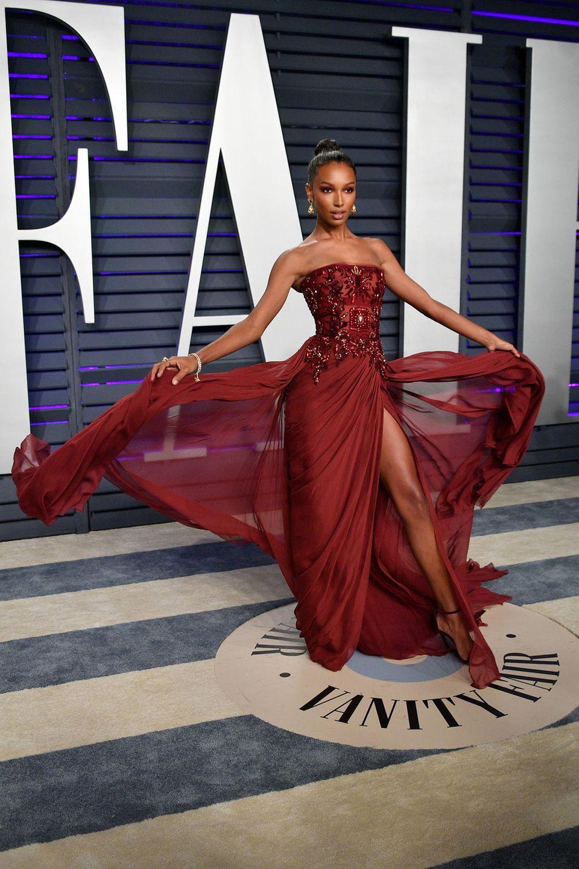 Schwungvoll in sattem Weinrot wirbelt Jasmine Tookes über den Red Carpet der Vanity Fair Party.