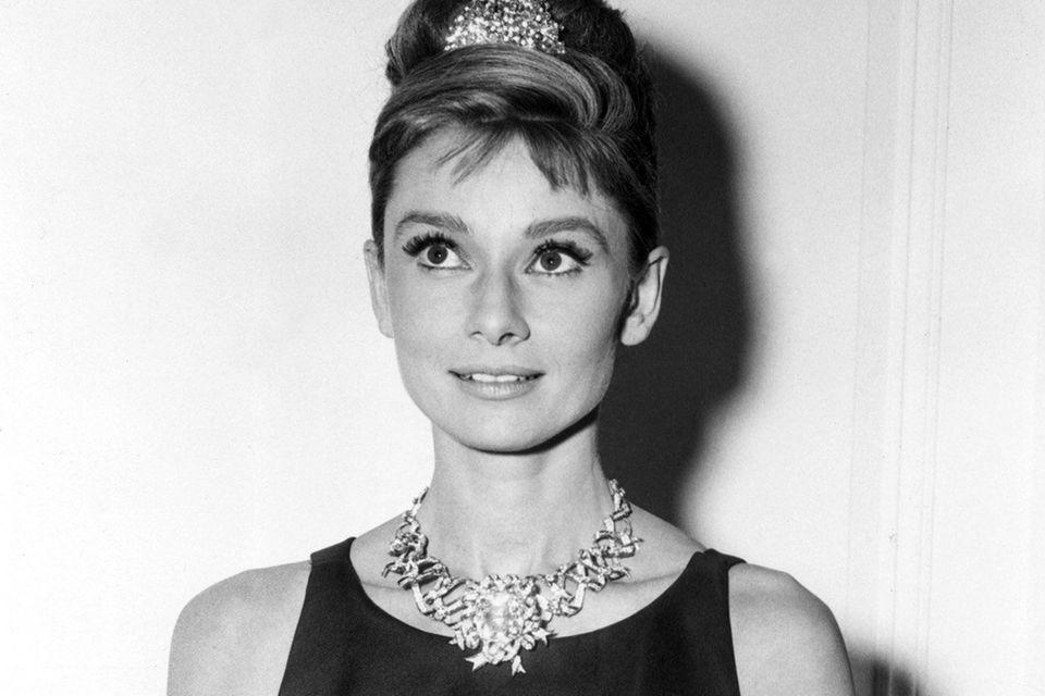 """In 1962 ist der gelbe Diamant noch Teil einer Brosche, die an einer opulenten Kette befestigt ist. Audrey Hepburn trägt sie zum Pressetermin von """"Frühstück bei Tiffany""""."""
