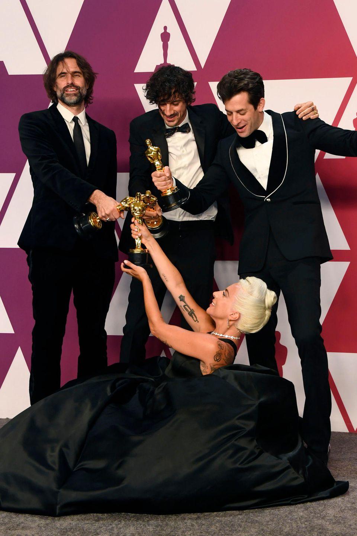 """Andrew Wyatt, Anthony Rossomando, Lady Gaga und Mark Ronson lassen sich mit ihren Goldjungen für den """"Besten Original Song"""" aus """"A Star is Born"""" fotografieren."""