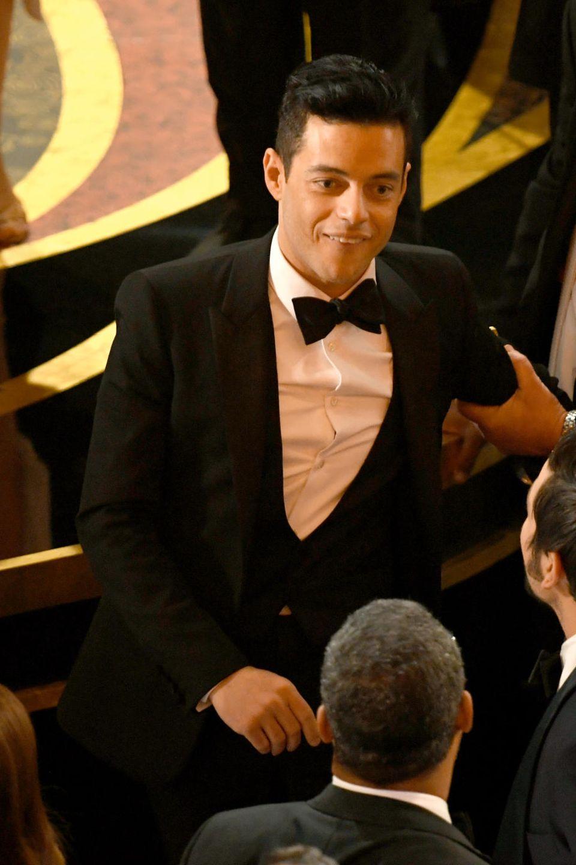 Ein anderer Gast der Oscars hilft Rami Malek auf.