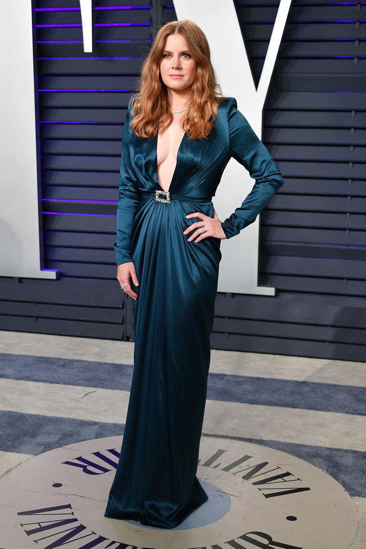 Zum Weiterfeiern steigt Amy Adamsauf dieses petrolfarbene Satin-Kleid mit sexy Dekolleté um.