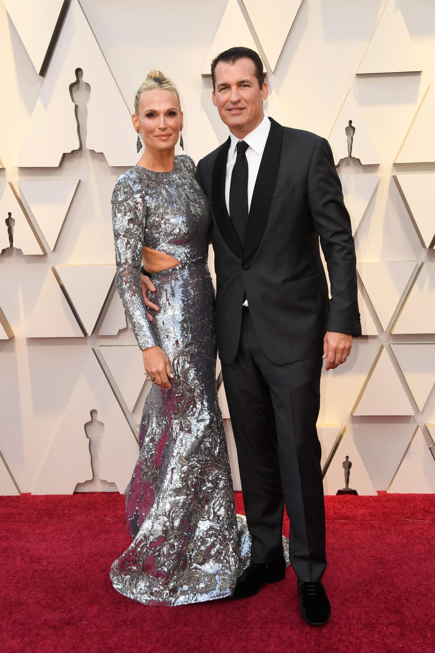Während sich Scott Stuber im klassischen Anzug eher zurückhält, trumpft Molly Sims in einem silbernen Paillettenkleid wundervoll auf.