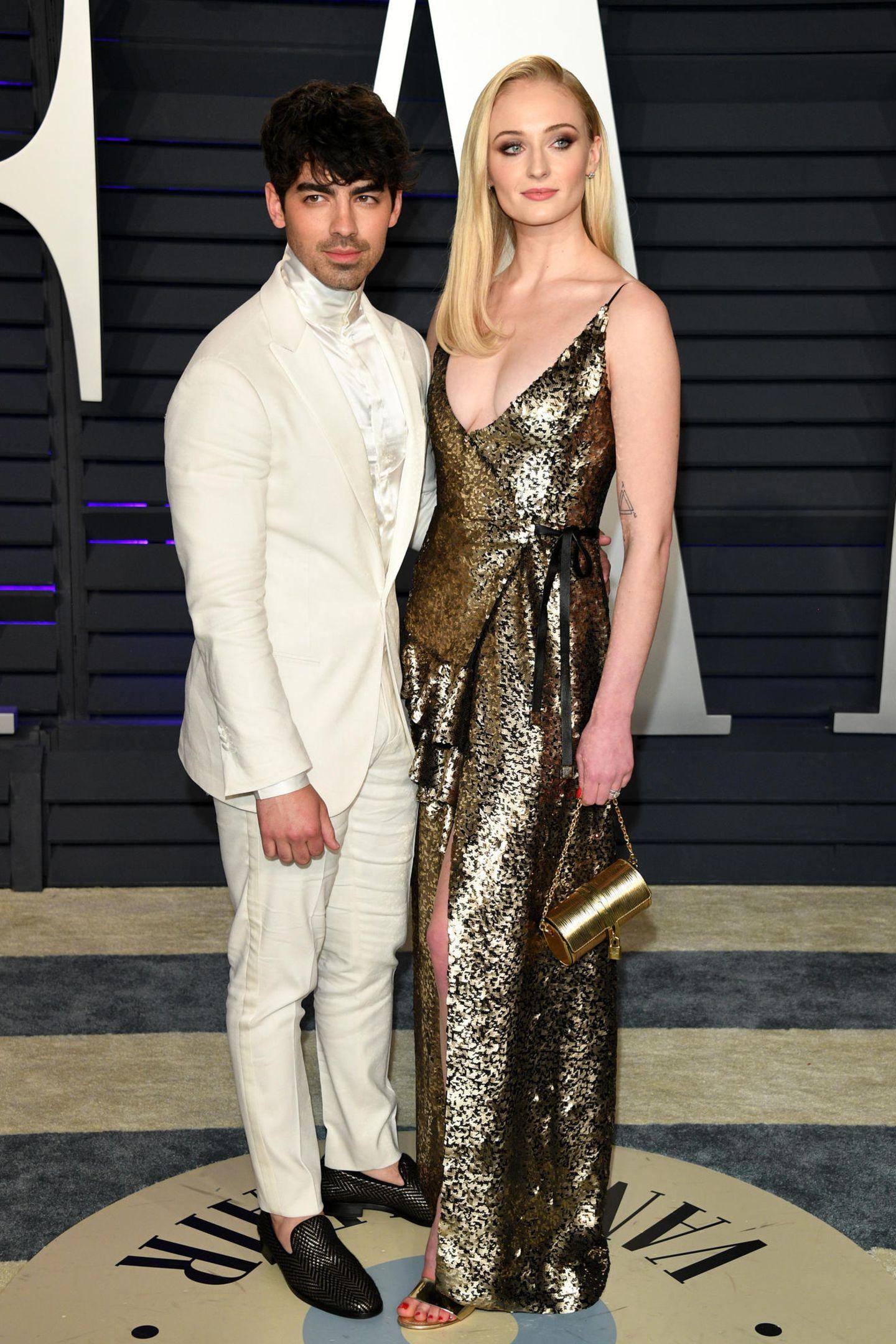 Joe Jonas und Sophie Turner wagen beide etwas: Er kommt im komplett weißen Anzug, sie setzt ganz und gar auf Gold.