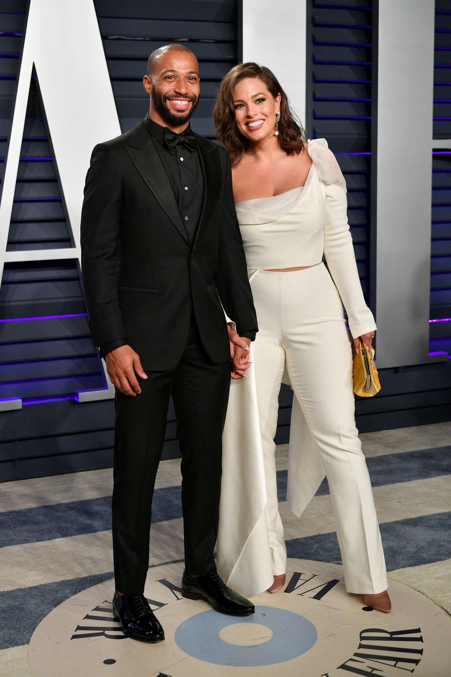 Justin Ervin und Ashley Graham setzen auf Kontraste. Er kommt in einem komplett schwarzen, sie in einem hellen Anzug.