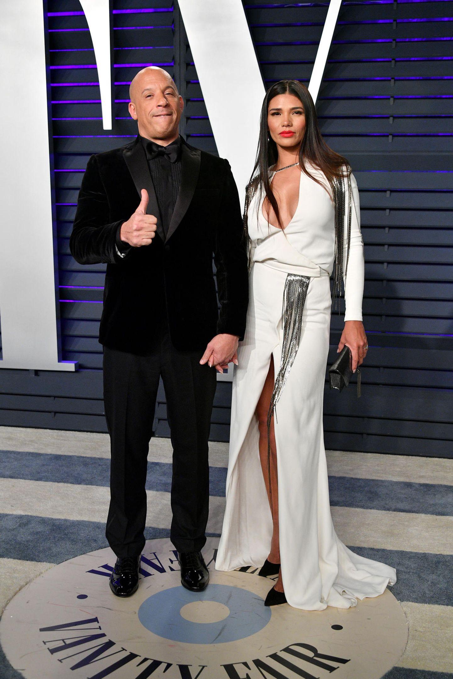 Vin Diesel bleibt selbst im eleganten Anzug seinen coolen Posen treu. Ehefrau Paloma Jimenez wirkt daneben eher sexy. Das liegt nicht zuletzt an ihrem tiefen Dekolleté und dem knallroten Lippenstift.