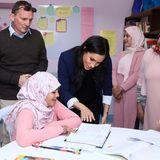 Nach der Zeremonie lässt sich Meghan von einer Schülerin ihre Unterlagen zeigen und wirft einen interessierten Blick in das aufgeschlageneSchulbuch.