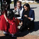 Glücklicherweise konnten die Reporter auch diesen niedlichen Moment einfangen: Meghan und Harry knien sich zu ihren kleinsten Fans, die gespanntauf die Royals warten. Besonders niedlich: Die beiden Mädchen sind im Partnerlook gekommen, tragen beide das gleiche rote Kleid mit Schleife auf dem Rücken.
