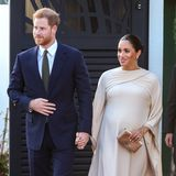 Am Abend wird es noch glamouröser: Harry und Meghan zeigen sich beim Besuchder britischen Botschaft in Abendgarderobe. Während der Prinz einen dunkelblauen Anzug wählt, zeigt sich Meghan in einem cremefarbenen Abendkleid von Dior. Das Dress ist - wie ihr Kleid am Tag zuvor - mit einem Cape ausgestattet. Zu dem aufregenden Kleid kombiniert Meghan eine goldene Clutch sowie gleichfarbige Pumps, beides ebenfalls von Dior.