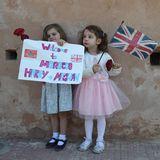 Auch in den Gärten werden Harry und Meghan von zwei besonders niedlichen Fans erwartet. Die kleinen Mädchen halten nicht nur die Flagge Großbritanniens, sondern auch ein selbstgebasteltes Plakat mit Grüßen für die Royals in den Händen.