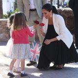 Als Geschenke für die Royals haben die Kleinen zusätzlich Blumen mitgebracht. Trotz Babykugel lässt es sich Meghan nicht nehmen, sich zu den Mädchen zu knien und mit ihnen auf Augenhöhe zu sprechen.