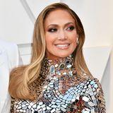 Besondere Augenblicke: Jennifer Lopez macht keine halben Sachen, was ihren Oscar-Look angeht - deshalb kombiniert sie zu ihrem funkelnden Kleid auch einen absolut glamourösen Beauty-Look. Ihre Haare trägt J. Lo akkurat geföhnt, ihre Augen sind in dunklen Brauntönen stark betont und auf ihren Lippen schimmert ein hübscher Nude-Ton.