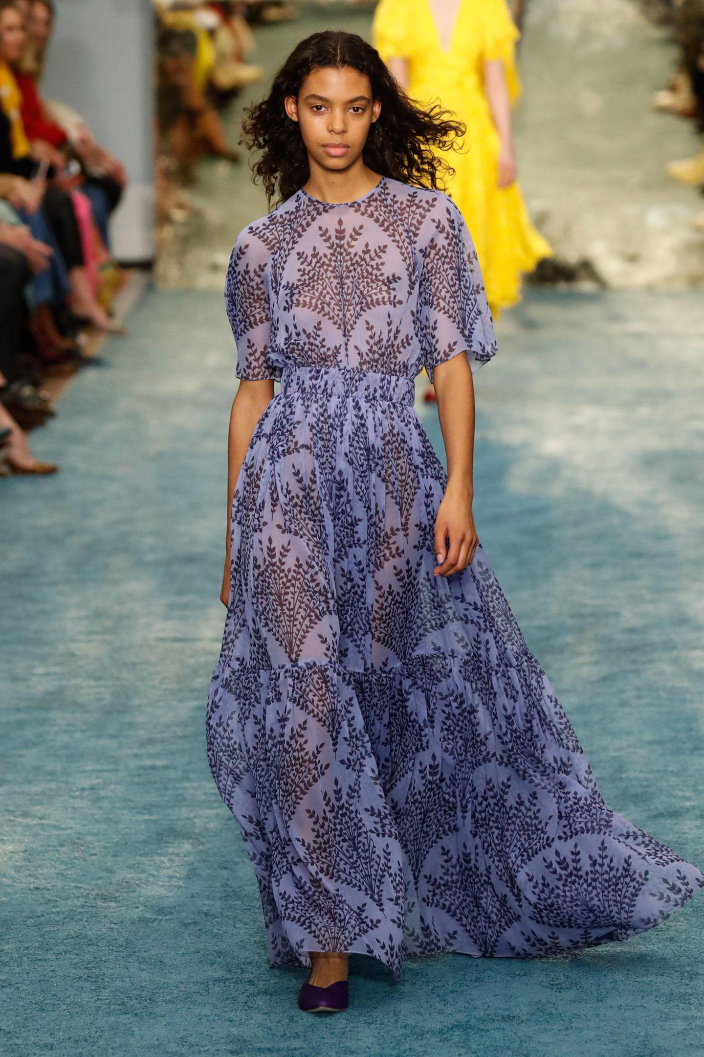 Bei derModenschau Frühjahr/Sommer 2019 von Carolina Herrera zeigt das Model den Entwurf aus einem feineren, transparenten Stoff. Das florale Ornamentmuster und die Maxilänge sind schon beimOriginal wunderschön.
