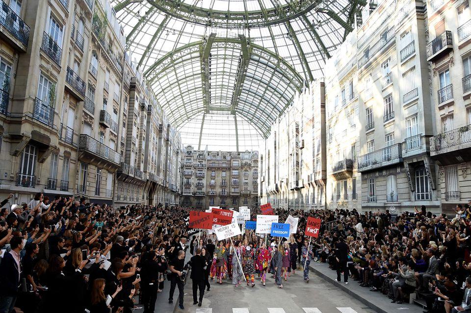 Demonstrieren können die Franzosenund Karl Lagerfeld auch! Für den feministischenAnstrich mit klaren Plakat-Botschaften gibt es aber auch Kritik: Lagerfeld nutze die Debatte für PR-Zwecke.