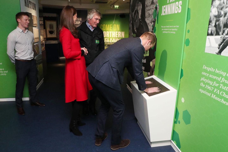 Prinz William und Herzogin Catherine lernen Nordirlands ehemaligen FußballstarPat Jennings kennen, der als einer der besten Torhüter aller Zeiten gilt und der Thronfolger vergleicht seinen Handabdruck mit dem des Star-Kickers.
