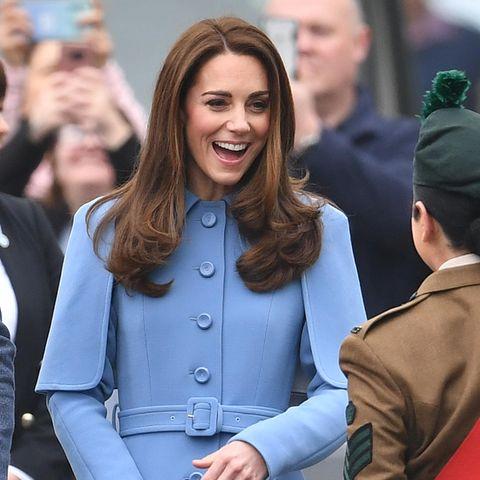 Die Cape-Form, die Knöpfe und der schmale Gürtel betonen die schmale Silhouette der Herzogin perfekt. Ihr brünettes Haar fällt ihr in perfekten Wellen über die Schultern.