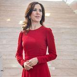 Sie trägt ein midilanges, schlichtes Kleid von Dolce & Gabbana. Dazu kombiniert sie beige Pumps und funkelnde Ohrringe.
