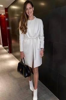 Zum Abendessen trägt sie ein weißes Kleid mit farblich passendem Mantel. Dazu kombiniert sie coole, weiße Boots und eine schicke, schwarze Handtasche rundet den Look ab.