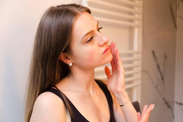 """Mit den Fingerspitzen """"drückt"""" Tabea den Ampullen-Inhalt portionsweise in ihre Haut ein. Das gelige Serum zieht direkt ein und hinterlässt einen sofortigen Effekt. Tabeas Haut wirkt direkt praller."""