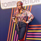 Tyra Banks setzt sich in Jeans und bunterBluse mit passendem Kopftuch in Szene.