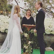 In einem zarten Traum in Weiß gibt Ashley Bush ihrem Verlobten Julian LeFevre das Ja-Wort. Ein langer Schleier im offenen Haar und die elegante Transparenz des Kleides passen perfekt zum klassischen Stil der Hochzeit, die in einem Museum in Austin, Texas, stattfand.