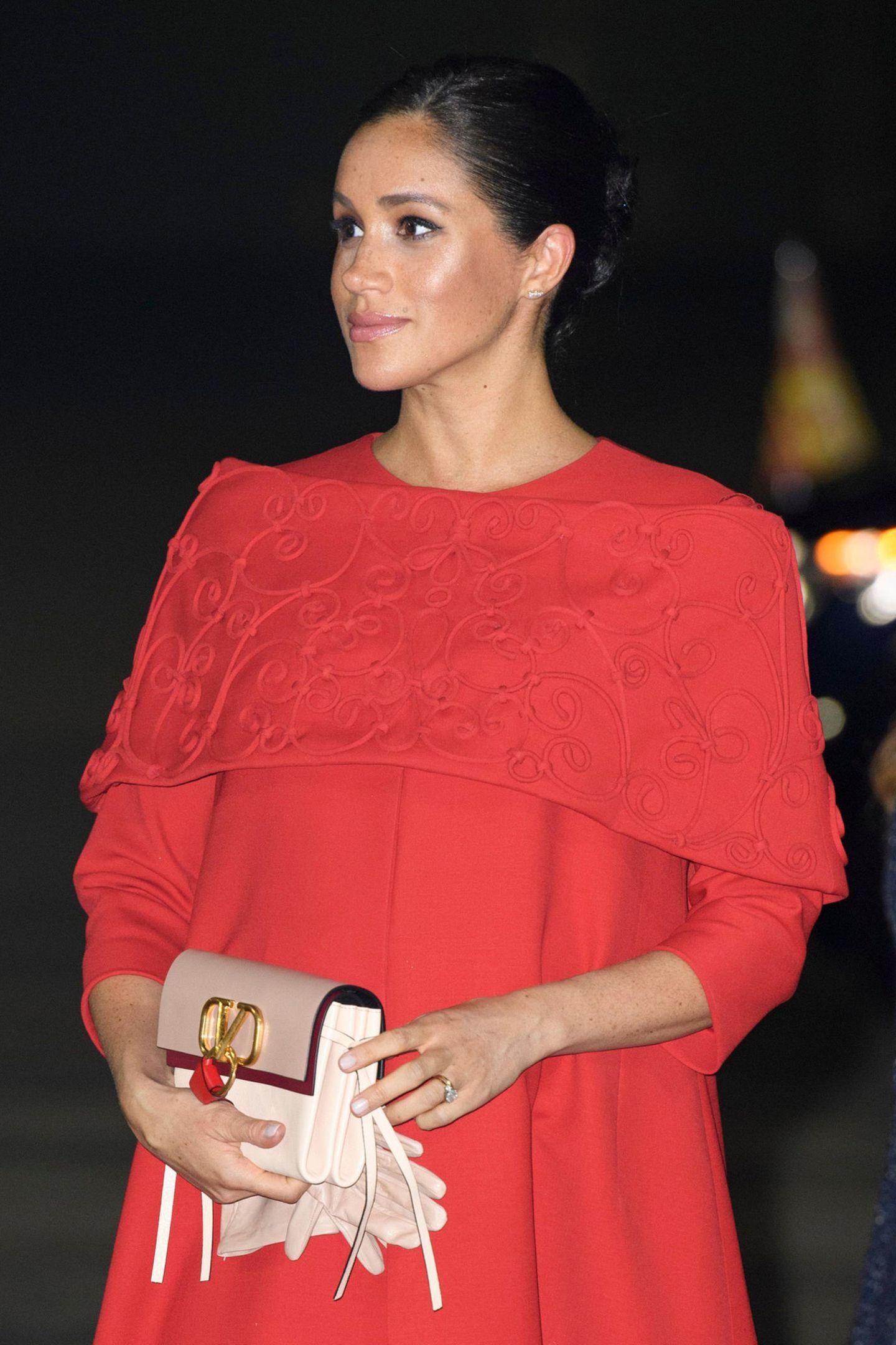 Während ihrer Reise nach Marokko zeigte sich auch Herzogin Meghan in einem Komplett-Look von Valentino. Passend zu ihrem Cape-Kleid hielt sie die rosafarbene Valentino-Clutch mit rotem Bommel in der Hand.