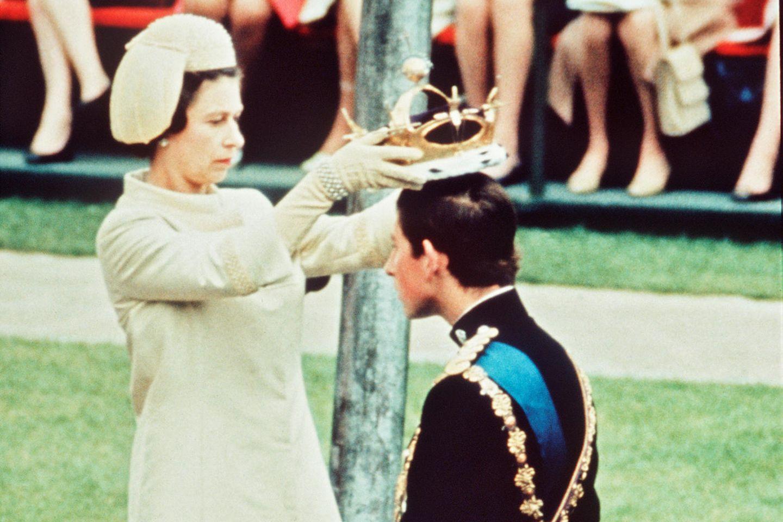 """Am 1. Juli 1969 wird Prinz Charles von seiner Mutter Queen Elizabeth zum """"Prinz of Wales"""" ernannt. Zwar sehen wir hier keine offizielle Krönung, aber eine entsprechende Kopfbedeckung gab's trotzdem für den damals 20-Jährigen."""