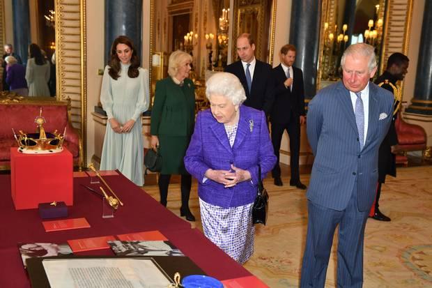 """Queen Elizabeth und Prinz Charles (vorne) betrachten die Insignien, die die Königin ihrem Sohn am 1. Juli 1969 bei seiner offiziellen Ernennung zum """"Prince of Wales"""" überreichte. Auch Herzogin Catherine, Herzogin Camilla, Prinz William und Prinz Harry sind dabei. Die Royals haben sich am 5. März 2019 im Buckingham Palast versammelt, um den 50. Jahrestag der Ernennung Charles' zu feiern"""