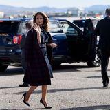 Melanias Reise geht weiter: Am Flughafen von Las Vegas zeigt sie sich in einem dunkelblauen Kleid, über das sie sich einen passenden Mantel von Calvin Klein geworfen hat. Mit wehendem Haar winkt sie den Fotografen.