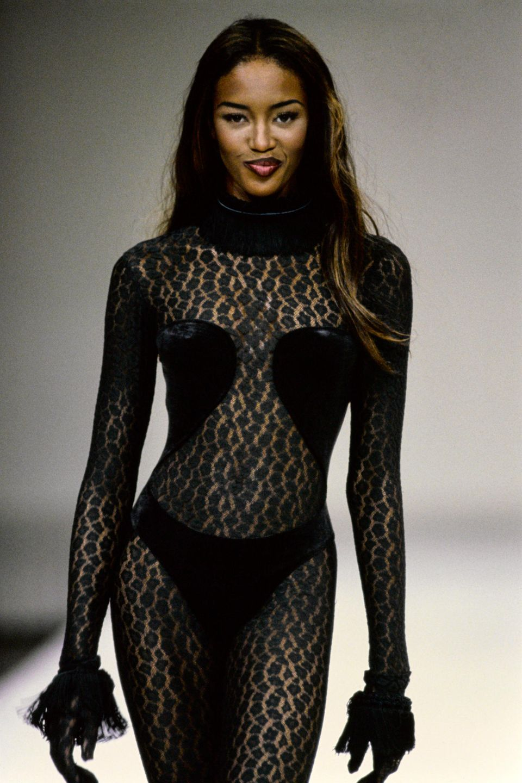 Bereits im Jahr 1991 stolziert Naomi Campbell in dem gleichen sexy Leo-Bodysuit von ModeschöpferAlaïa über den Catwalk. Das Supermodel ergänzt den Look damals noch um federbesetzte, schwarze Lederhandschuhe.