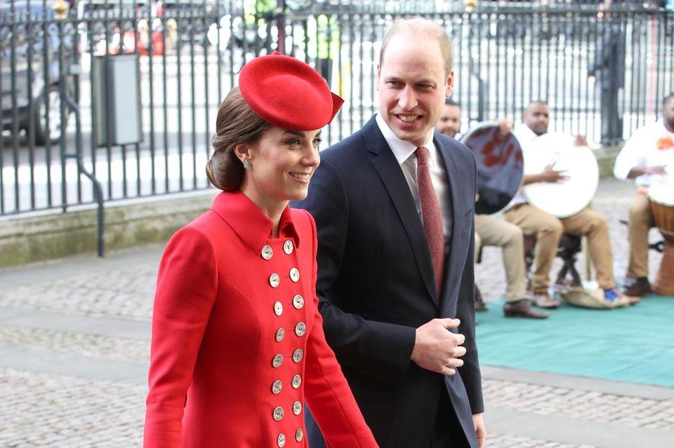 Herzogin Catherine entscheidet sich für ein knallrotes Mantelkleid von Catherine Walker mit auffälligen Knöpfen.