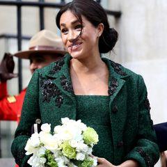 Die hochschwangere Herzogin von Sussex hält müde, aber strahlend einen Blumenstrauß und ihren Babybauch.