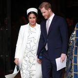 """Für Herzogin Meghan ist der Gottesdienst am Nachmittag bereits der zweite Termin am """"Commonwealth Day"""". In einem weißen Kleid ( Preis 1.350 Euro) mit passendem Mantel (beides von Victoria Beckham) erscheint sie zusammen mit Prinz Harry bei Westminster Abbey. Clutch und Schuhe (ebenfalls von Victoria Beckham) sind dunkelgrün und passen so perfekt zu dem Kettendruck auf ihrem Kleid."""