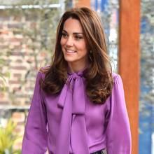 Zu ihrer lilafarbenen Gucci-Bluse kombiniert Herzogin Kate eine schwarze Highwaist-Hose von Jigsaw für rund 150 Euro sowie schwarze Wildleder-Pumps. In ihrer Hand trägt sie dieMidi Mayfair Bag im Farbton Taupe des Labels Aspinal of London im Wert von etwa 580 Euro.
