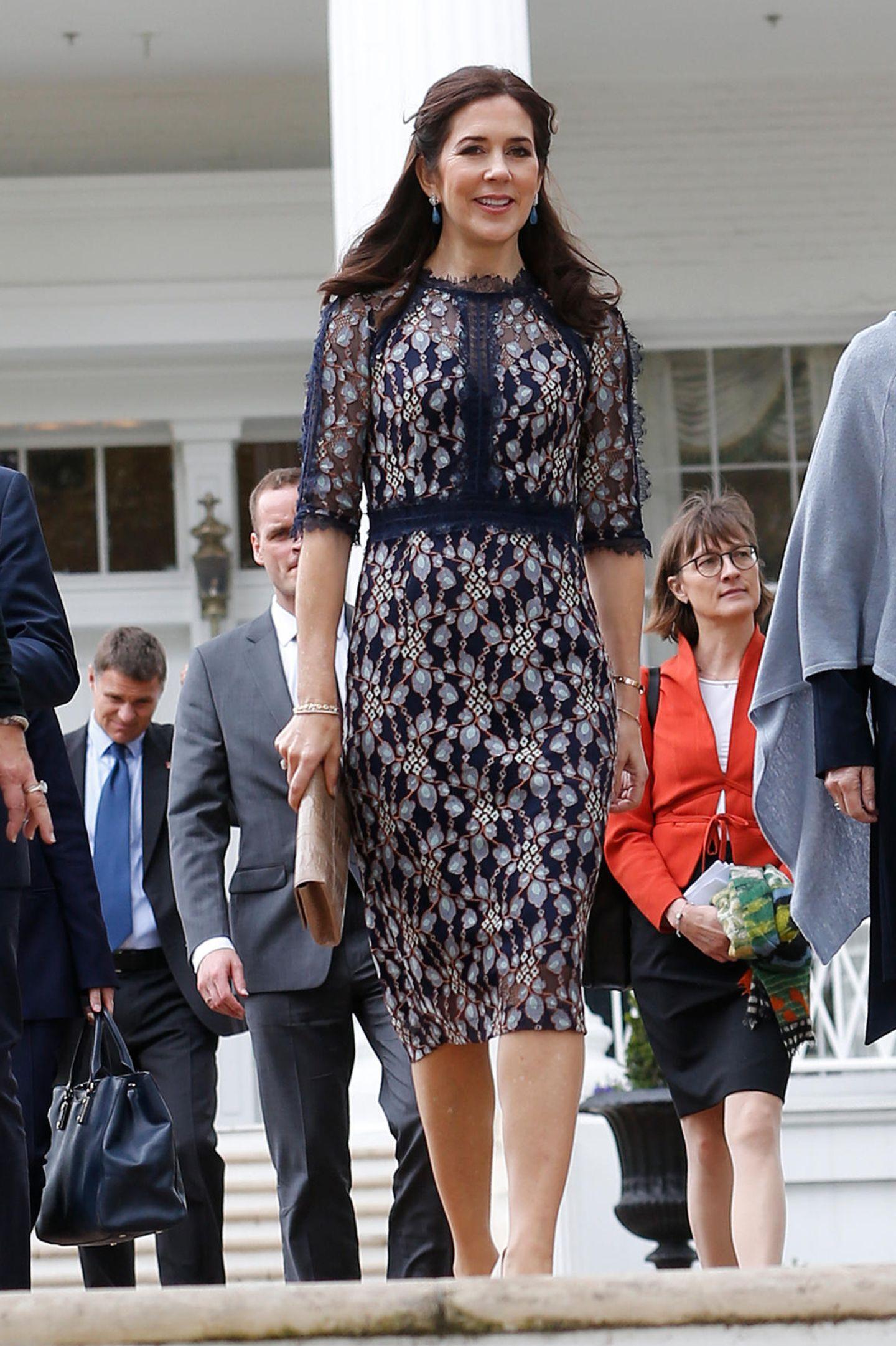 Im eleganten,dunkelblauen Etuikleidbeweist Kronprinzessin Marywieder einmal ihr gutes Händchen bei der Outfitwahl. Das bestickte, körperbetonte Kleid ist schick, aber nicht spießig und passt daher optimal für ihren Besuch beim Gouverneur.