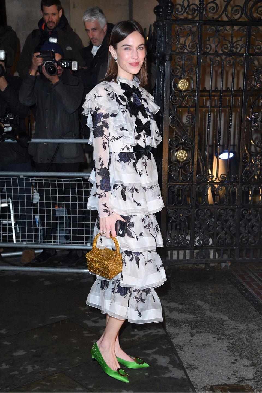 It-Girl Alexa Chung setzt beim Gala-Event der National Portrait Gallery auf ein romantisches Volant-Kleid von Erdem in Schwarz und Weiß, zu dem sie eine goldene Handtasche und knallgrüne Kitten Heels (ebenfalls Erdem) kombiniert.
