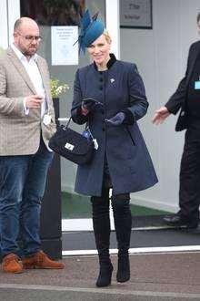 Farblich sehr zurückhaltend besucht Zara Tindall das Cheltenham Festival im verregneten England. Zu einem dunkelgrauen Mantel mit Stehkragen kombiniert sie schwarze Overknee-Stiefel und einen Hut in Petrolblau.
